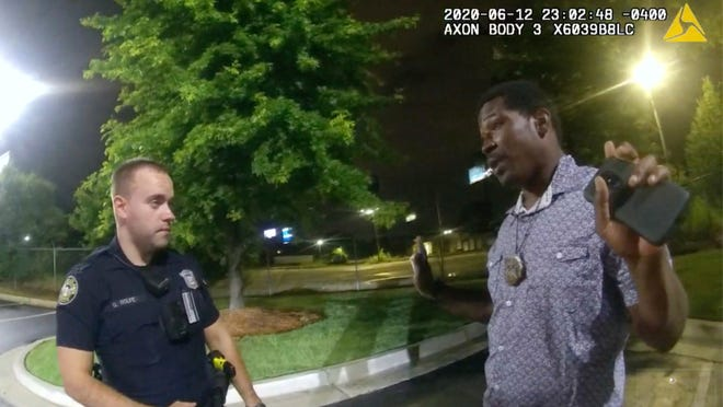 This screen grab taken from body camera video provided by the Atlanta Police Department shows Rayshard Brooks speaking with Officer Garrett Rolfe in the parking lot of a Wendy's restaurant, late Friday, June 12, 2020, in Atlanta. Rolfe has been fired following the fatal shooting of Brooks and a second officer has been placed on administrative duty.