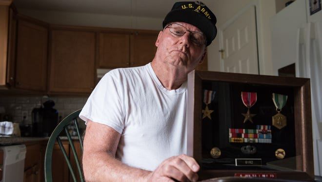 Jim Byrd, of Salisbury, poses for a photo holding his medals and ribbons at his home on Wednesday, Nov. 9, 2016.