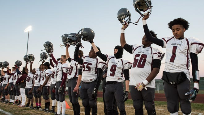 Snow Hill football players raise their helmets after the conclusion of the national anthem.