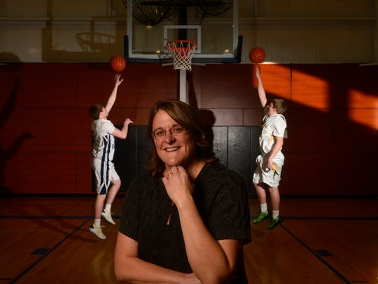 Marti Vining's four kids all have played basketball. Her youngest, Sam, shoots behind her.