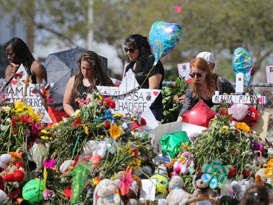 Mourners bring flowers as they pay tribute at a memorial