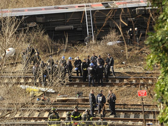 Emergency workers at the scene of a commuter train wreck on Dec 1, 2013 in the Bronx borough of New York. The train bound for New York's Grand Central Station derailed in the Bronx Sunday with at least four people reported dead after several rail cars left the tracks near the Spuyten Duyvil railroad station.