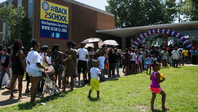 """People stand in a long line during the Shelby County Schools block party at 160 S. Hollywood in August. School enrollment at SCS has increased slightly for the first time since the """"de-merger"""" with the suburban schools in 2014."""