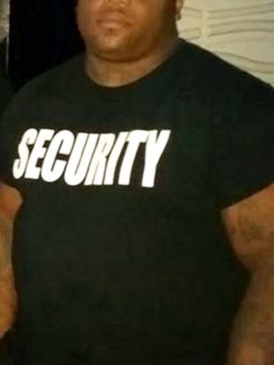 Dressed in his security guard T-shirt, Corey Bryan poses for a photo inside Vinny's Goodtimes bar where he was working as a bouncer when he was shot and killed Saturday morning. Two York men have been charged in his death.