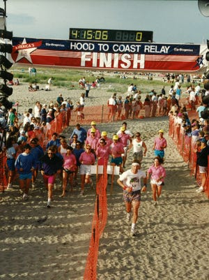 """Salem dentist Mark Rogers and his team """"The Donner Party"""" all in pink t-shirts and yellow hats cross the finish line sometime in the early '90s."""