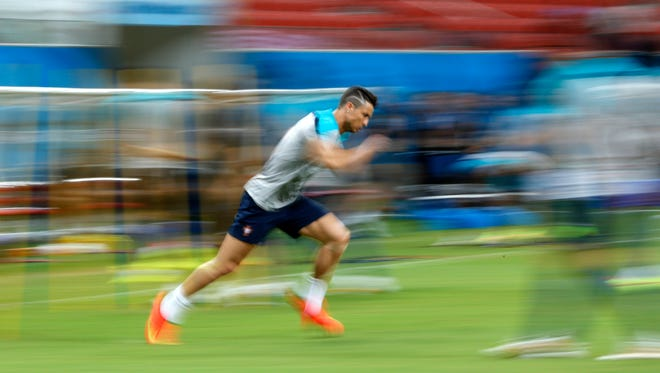 In this photograph taken with a slow shutter, Portugal's Cristiano Ronaldo works out during a training session Saturday at Arena Amazonia.