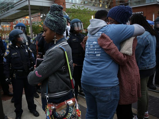 Local resident Tyannis Carter, right, gets a hug from