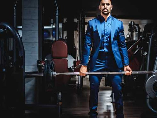 Man in a suit lifting weights.