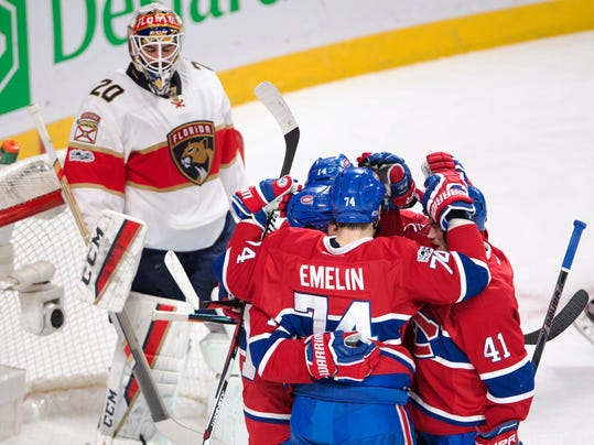 Montreal Canadiens center Tomas Plekanec (14) celebrates with teammates Alexei Emelin (74)Brendan Gallagher (11) and Paul Byron (41) in front of Florida Panthers goalie Reto Berra (20) after scoring the second goal during first-period NHL hockey game action in Montreal, Thursday, March 30, 2017. (Ryan Remiorz/The Canadian Press via AP)