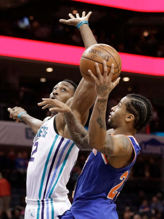 New York Knicks' Trey Burke (23) shoots against Charlotte Hornets' Dwight Howard (12) during the second half of an NBA basketball game in Charlotte, N.C., Monday, March 26, 2018. (AP Photo/Chuck Burton)