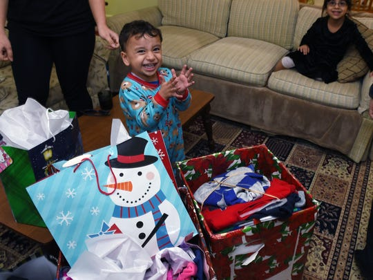 Syrian refugee Mahmoud Nakshou, 3, becomes excited after receiving presents from United Methodist Communications staff on Thursday, Dec. 17, 2015.