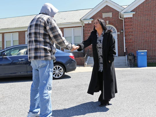 Natalie Greene, who is running for Delaware City's Town Council, shakes hands with a man who came out to vote Tuesday. State election officials said elections for three of the city's five council seats were postponed on Monday because of an error in the legally mandated election notice.