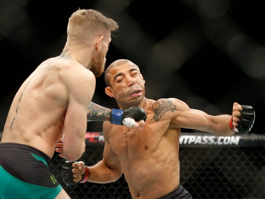 Conor McGregor connects with the left that dropped Jose Aldo in their featherweight title bout at UFC 194.