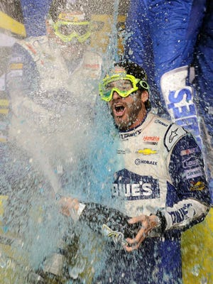 Jimmie Johnson celebrates after wining the NASCAR Sprint Cup auto race and season title Sunday, Nov. 20, 2016, in Homestead, Fla.