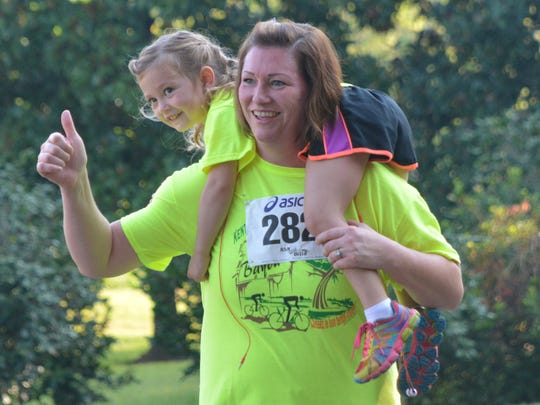 Brette Lutz carries daughter Celine Lutz and gives a thumbs up to the Youth Challenge cheering squad as she finishes walking the 5K which was part of the Le Tour de Bayou.