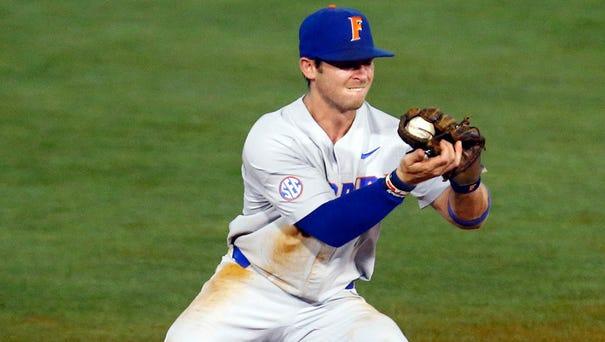 Florida shortstop Deacon Liput fields a ground...