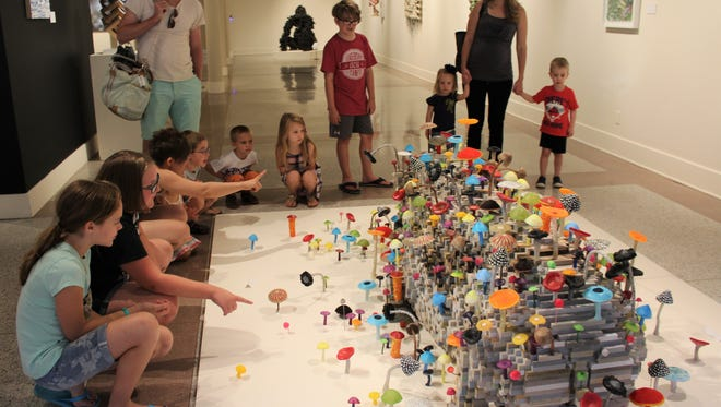 """A family outing Tuesday to The Grace Museum led to an extended look at Shawn Smith's white rhino piece titled """"Harmony of Decay."""" The animal is engulfed by realistic and colorful mushrooms."""