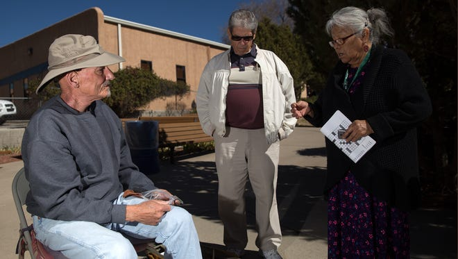 Bruce Burks, left, talks with Benny Valencia and Berniece Etcitty about various types of arrowheads during a flintknapping workshop on Thursday at the Bonnie Dallas Senior Center in Farmington.