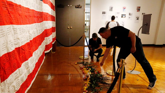 "Jose Gonzalez, a retired 22 year Army veteran lays a flower at the base of the American flag that is part of the ""We Will Never Forget,"" gallery exhibit at the Union Gallery on the University of Texas at El Paso campus. The exhibit will continue through September 23."