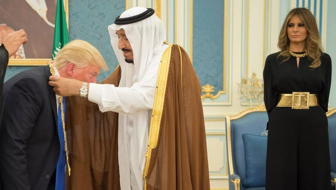 First lady Melania Trump looks on as President Trump receives the Order of Abdulaziz al-Saud medal from Saudi Arabia's King Salman bin Abdulaziz Al Saud (C), during a welcome ceremony at the Saudi Royal Court in Riyadh, Saudi Arabia, on May 20, 2017. According to White House Wardrobe on Twitter, Mrs.Trump wore a black Stella McCartney jumpsuit with a wide gold belt and a  gold necklace.