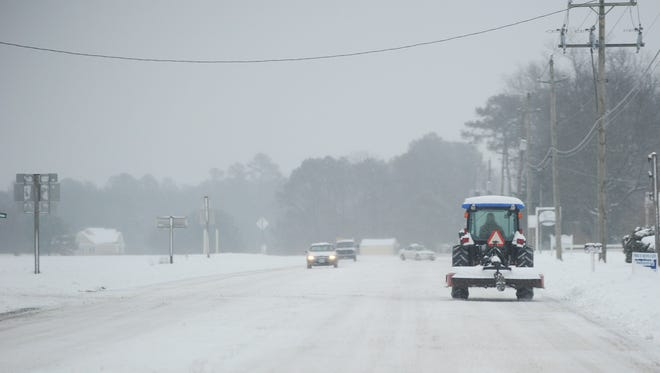 A tractor travels through the snow on Market Street in Onancock, Va. on Tuesday morning, Feb. 17, 2015. Areas in Accomack County received about 6-7 inches of snow overnight according to the National Weather Service.