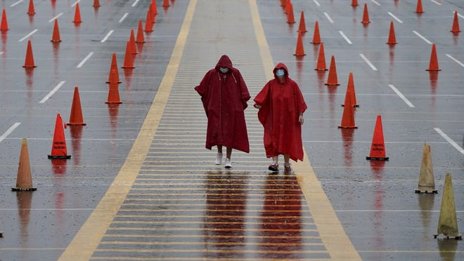 In this Aug. 29 file photo, fans walk through a parking lot at Arrowhead Stadium marked with traffic cones to keep fans from parking too close together during NFL football training camp for the Kansas City Chiefs in Kansas City, Mo.
