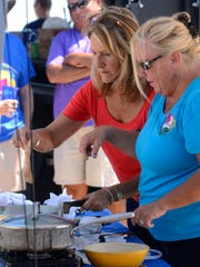 Dawn Phillips and Rhonda Dorfan of the Pensacola Beach Women's Club, cook some lionfish during the team challenge cook-off Saturday during Taste of the Beach at Pensacola Beach.The teams had 30 minutes to cook a dish with lionfish and a mystery ingredient, then it was judged by five Pensacola Celebrity Chefs, Gus Silivos, Dan Dunn, Irv Miller, Jim Shirley and Frank Taylor.