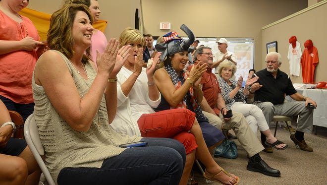 Angie Byers, sitting left, and others applaud early voting numbers as they watch election night coverage at the Madison County Republican Party headquarters in Jackson on Thursday.