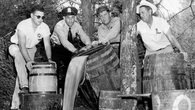 Rutherford County Deputy Sheriff Dudley Comer, left, Murfreesboro police Patrolman Henry Carlton, Deputy Lester Singleton and Sheriff W.H. Wilson pour out mash seized in a raid Aug. 29, 1957, on two moonshine stills near Murfreesboro, Tenn.