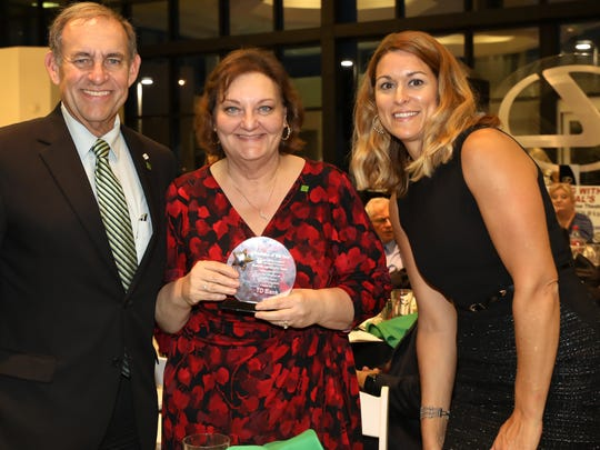 Rene Arteaga (left), vice president of TD Bank, and colleagues accept a Retail Sales award.