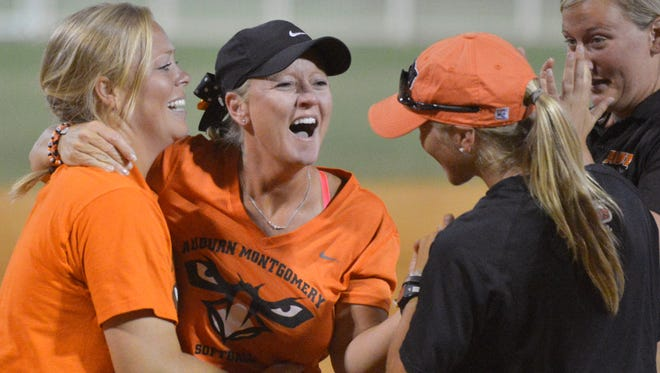 AUM coach Chris Steiner-Wilcoxson, black cap, celebrates with players and staff after the Warhawka defeated WIlliam Carey 10-6 to win the NAIA Softball World Series on Thursday in Columbus, Ga.