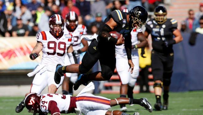UCLA quarterback Brett Hundley leaps over Virginia Tech defender Kyshoen Jarrett.