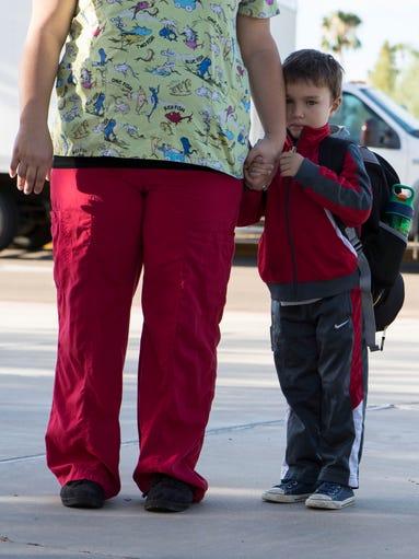 Evan Fincher, 6, holds onto his mother, Lauren Fincher,