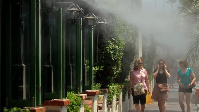 Linda Westrick of Calimesa (left) walks under the misters with daughters Annie Westrick (middle) and Tina Lozano (right) in front of Las Casuelas Terraza along South Palm Canyon in Palm Springs, Calif. on Tuesday afternoon, July 9, 2013.