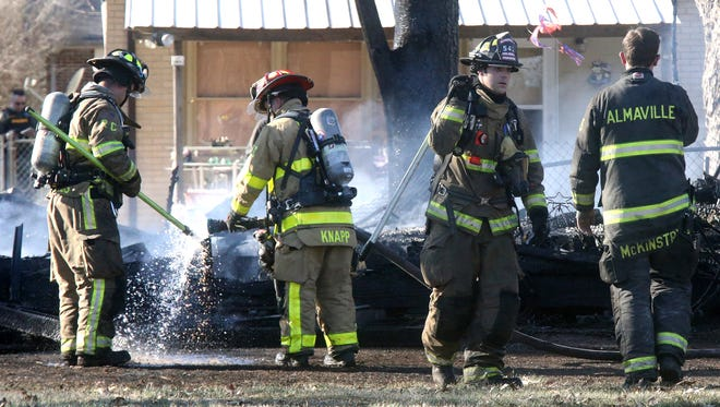 Firefighters work the scene of grass fire that burned down a shed containg family Christmas items, on Tuesday, Jan. 31, 2017.
