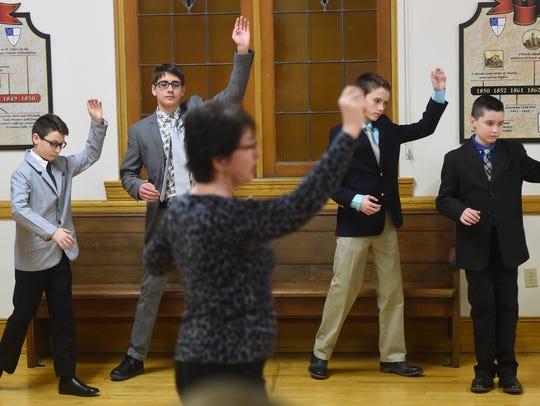Dance instructor Vera Kywa leads a lineup of boys through