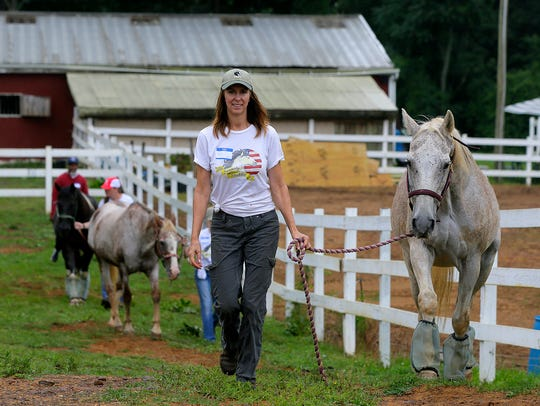 Rene Stone, owner, leads her horse, Tristan, to an