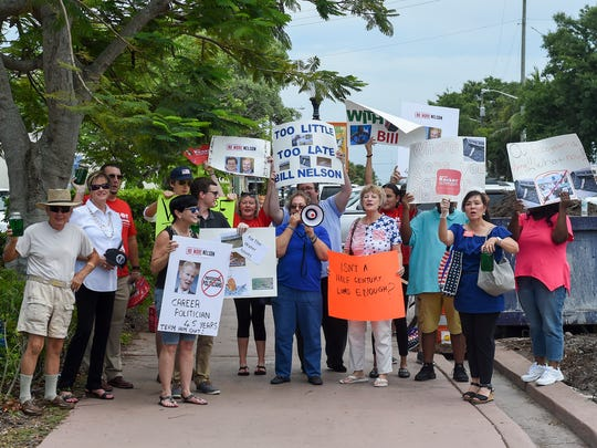 Protesters stand outside City Hall in Stuart, Florida, where senior U.S. Sen. Bill Nelson, of Florida, discussed toxic discharges in local waterways and ways to stop them Thursday, July 5, 2018, with city, county and state officials, ecological and medical experts, and local business owners and residents.