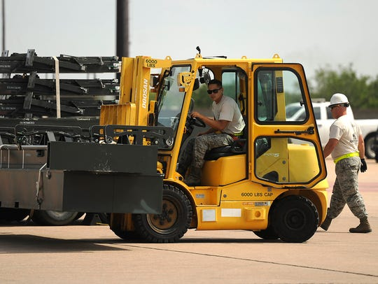 A Dyess airman uses a forklift to move equipment in
