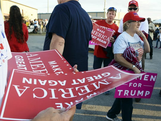 Signs are readily available for spectators as they head into the amphitheater at the Central Florida Fairgrounds to see President-elect Donald Trump.