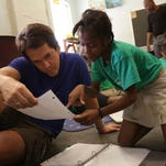 Mitch Albom, left goes over what Bianka Moricette, 9 has been doing in class at The Have Faith Haiti Mission in Port Au Prince, Haiti in November 2014. Mitch Albom began going to Haiti a few weeks after the 2010 disaster and now operates the orphanage/mission raising 40 children who are taught in both French and English.