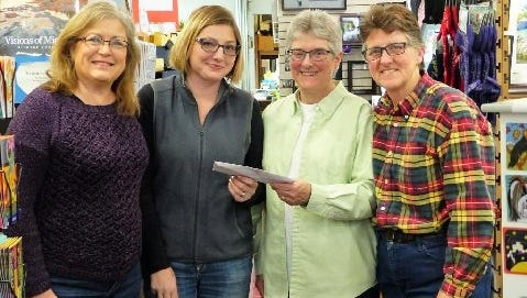 Janice Dumas and Andrea Perry of the VFAA SHAC accept a check for the proceeds from the Give Back Friday Milford community fundraiser from Barbara Moorehead and Leslie Watson of Main Street Art.