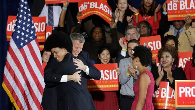 Democratic Mayor-elect Bill de Blasio embraces his son Dante on stage after he was elected the first Democratic mayor of New York City in 20 years in the Brooklyn borough of New York, Tuesday, Nov. 5, 2013.  De Blasio, who beat out Republican Joe Lhota by a large margin, follows the three-term reign of Republican-turned-independent billionaire Michael Bloomberg, and Republican Rudy Giuliani, who led the city in the wake of the 2001 terrorist attacks. (AP Photo/Kathy Willens)
