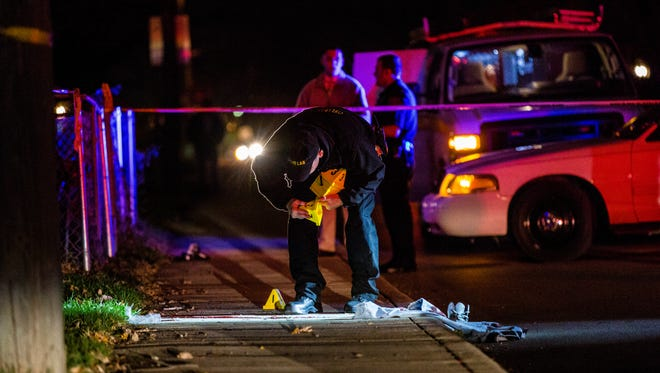 A crime lab technician places evidence markers next to clothing belonging to a man who was critically injured Friday night in a shooting on the Southeastside.
