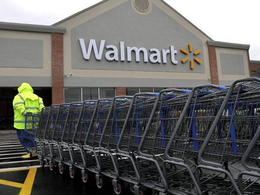 Associated Press/Steven Senne - In this Tuesday, Nov. 13, 2012 photo a worker pulls a line of shopping carts toward a Walmart store in North Kingstown, R.I.  (AP Photo/Steven Senne)