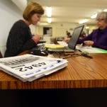 Holly Manuel, a tax preparer with the Volunteer Income Tax Assistance (VITA) program, works on Elizabeth Anderson's taxes on Friday, January 30, 2015.
