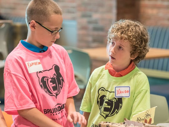 Kameron Cooper, left, and Xander Yoder sell candy at Kellogg Community College on Wednesday.