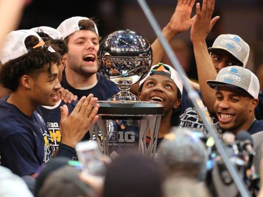 The Michigan Wolverines celebrate winning the Big Ten