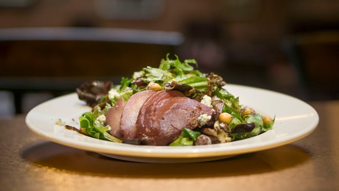 Chira's Poached Pear Salad arrives with caramelized onion, blue cheese, candied hazelnuts and a port-poached pear. Chira's Restaurant & Catering opened May 12 in the Reed Opera House.
