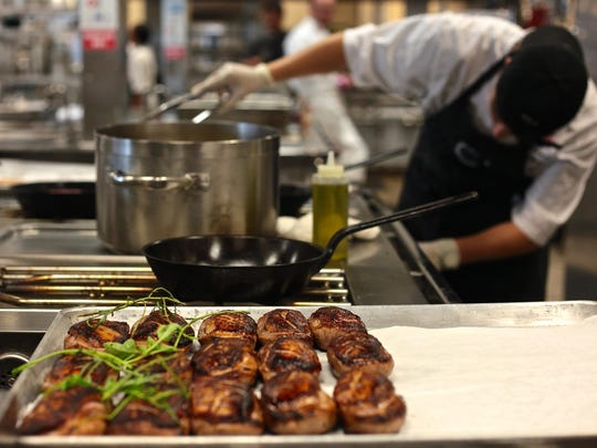 Blackhawk students representing two teams led by local Chefs, Herve Glin and Chris Mitchum, prepare specialty items including duck, scallops and avocado during a culinary showdown at La Quinta High School, Thursday.